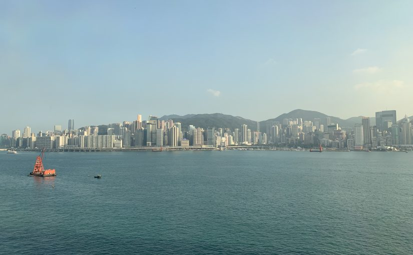 Boats pass by in Victoria Harbour as the Hong Kong cityscape looms behind.