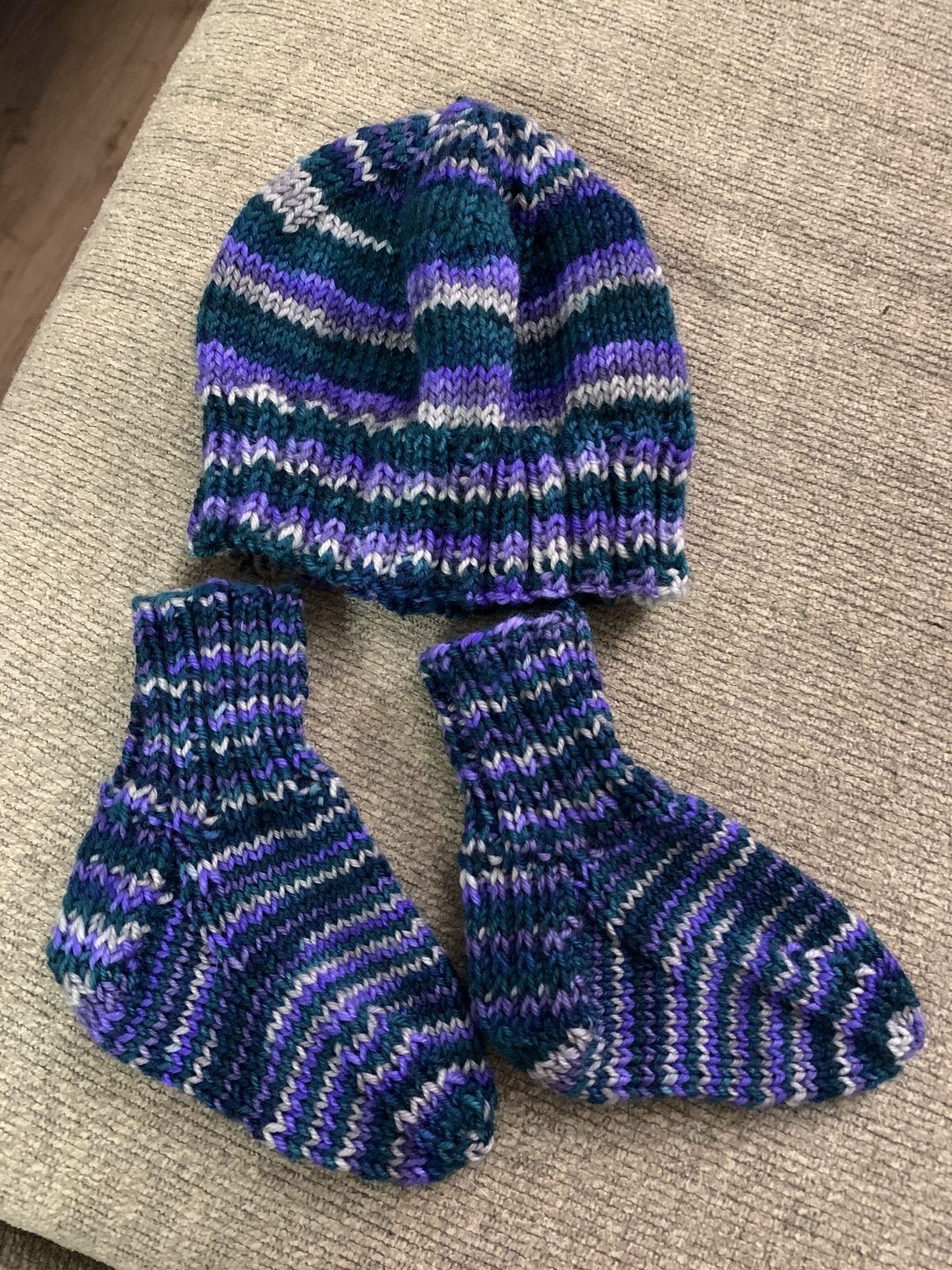 Baby hat and socks in vibrant green, purple, and gray stripes